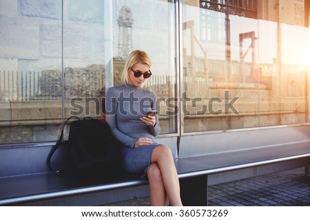 Stylish hipster girl chatting in network via smart phone with her friends while sitting on bus stop in summer day,fashionable woman tourist searching information about bus traffic using cell telephone - stock photo