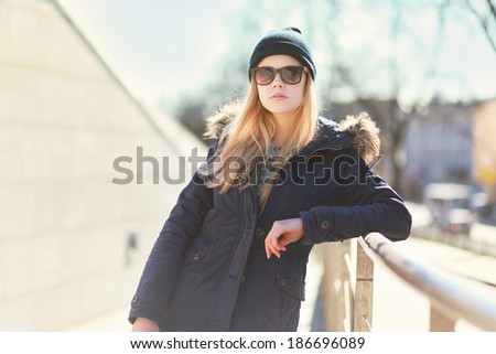 Stylish hipster girl posing in the city a warm day, bright sunshine, fashion photo - stock photo
