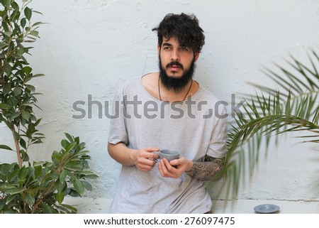 stylish hipster guy drinking a coffee outdoors - stock photo