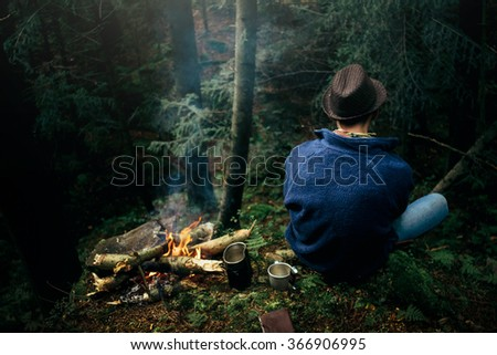 stylish hipster traveler camping in sunny forest in the mountains - stock photo