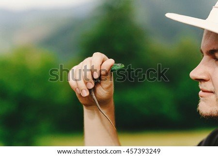 stylish hipster traveler holding green lizard in his hand in summer mountains,  travel   concept, space for text