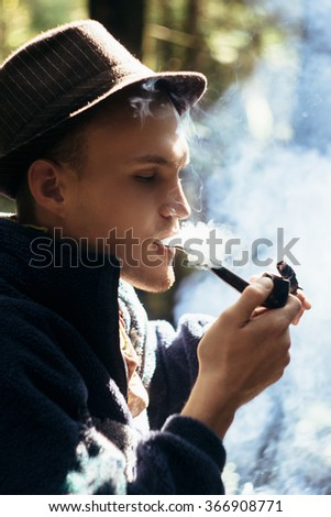 stylish hipster traveler smoking tobacco pipe in sunny forest in the mountains