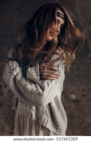 stylish hipster woman posing in knitted sweater. atmospheric windy sensual moment. boho country fashionable look.
