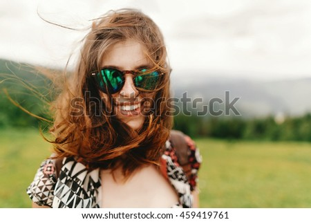 stylish hipster woman traveler with fashionable sunglasses and windy hair smiling  and having fun on top of mountains in summer, travel concept, space for text - stock photo