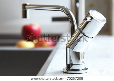 Stylish home interior sink tap and red apples - stock photo