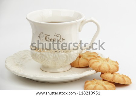 Stylish ivory cup of tea and some sweet round shape cookies