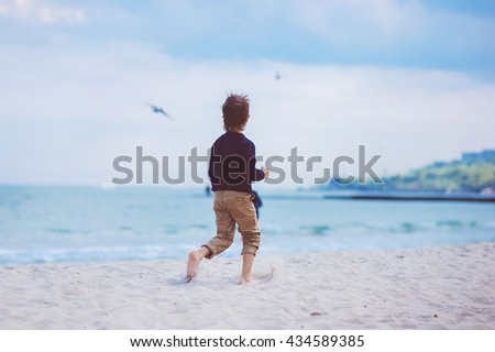 Stylish kid boy walking the tropical beach, Happy little boy walking near the sea, summertime.