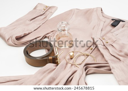 Stylish ladies beige dress with fashion accessories including a leather belt, gold bangles and bottle of perfume or scent laid out ready on a white background, low angle view - stock photo