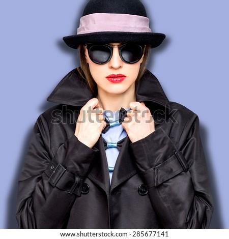 Stylish lady in fashionable hat and sunglasses over purple background - stock photo