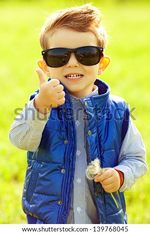 Stylish laughing baby boy with ginger (red) hair in trendy sunglasses and blue jacket standing in the park, holding dandelion and showing thumb up (ok). Hipster style. Sunny weather. Outdoor shot - stock photo