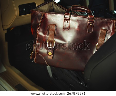 Stylish leather bag and a luxury car
