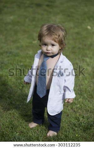 Stylish little baby boy with blonde curly hair in white unbuttoned shirt grey necktie and trausers standing barefoot on fresh green grass yard sunny day outdoor on natural background, vertical photo - stock photo