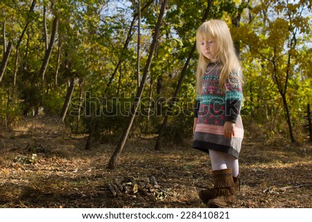 Stylish little blond girl in autumn fashion standing outdoors in woodland in her colorful jumper and leather boots staring to the side with a thoughtful expression, with copyspace - stock photo