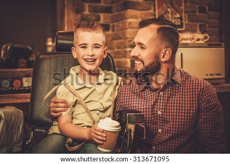 Stylish little boy and his father in a barber shop - stock photo