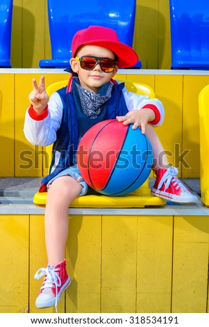 Stylish  little boy posing at basketball court - stock photo