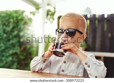 Stylish little boy wearing trendy sunglasses belonging to his Mum or Dad sitting on an outdoor patio sipping a soft drink from a tumbler as he plays at being grown up - stock photo
