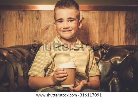 Stylish little boy with coffee mug