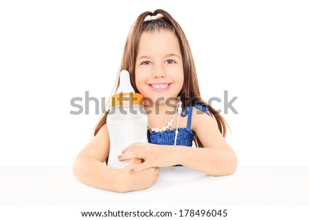 Stylish little girl holding a huge baby bottle seated at table isolated on white background - stock photo