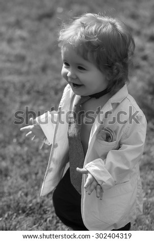 Stylish little smiling baby boy with curly hair in unbuttoned shirt necktie and trausers standing on fresh grass yard sunny day outdoor on natural background black and white, vertical photo - stock photo