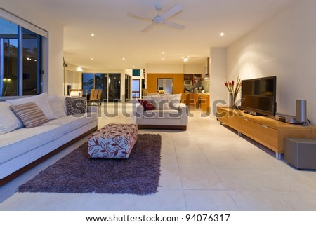 Stylish living room with couch and TV in a modern house - stock photo