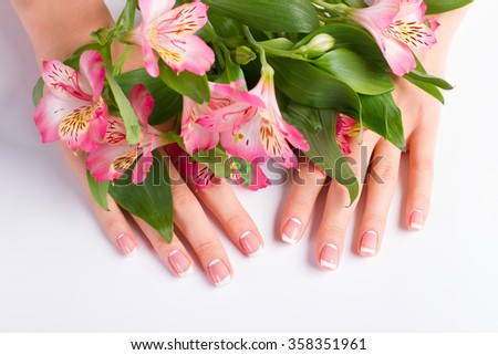 Stylish lunar french manicure on a background of freesia flowers.
