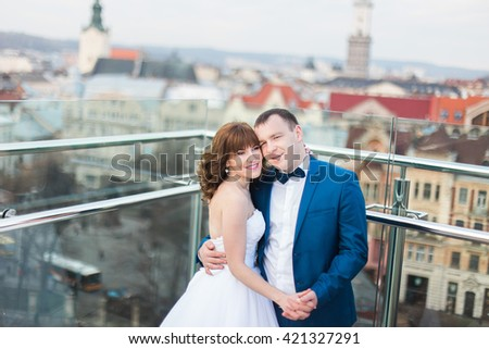 Stylish luxury bride and elegant groom hugging with tenderness on background of the old city Lviv