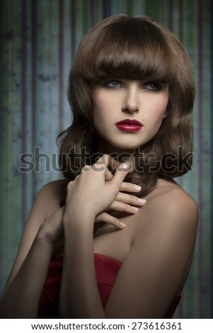 Stylish, luxury, brunette girl with beautiful, smooth hairstyle with straight fringe wearing red lipstick and astin top. She has got her hands on the chest.