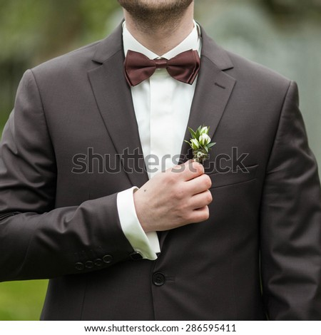 stylish luxury brunette  groom in a suit with a brown bow on the background garden