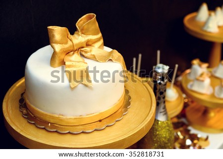 stylish luxury decorated candy bar with frosting cake and champagne at the golden birthday party, holiday celebration concept - stock photo