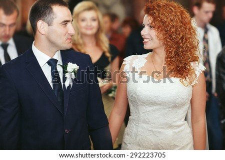 stylish luxury red haired bride and elegant groom holding hands, wedding ceremony in the old church