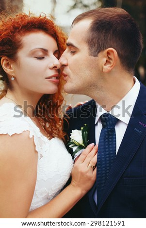 stylish luxury red haired bride and elegant groom, kissing in the autumn park, on the background of the old city Lviv