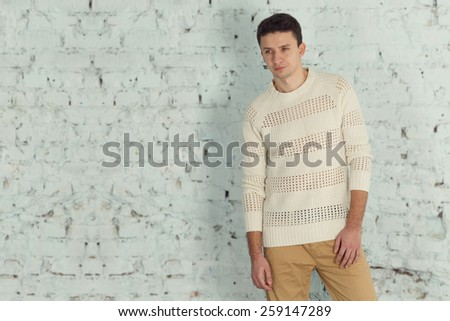 Stylish male model in a white jacket. Portrait of handsome caucasian brunette. Young modern man stands on a light background of a brick wall. American, European who works as a model. serious cheerful - stock photo