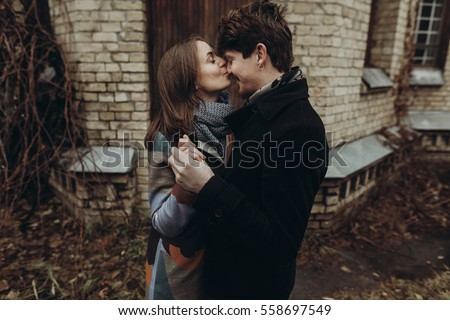 stylish man and woman kissing.romantic calm atmospheric moment. couple hugging gently in autumn park, showing true feelings. family togetherness concept