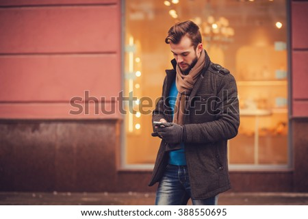 stylish man in a coat with a smartphone in the city. traveling - stock photo