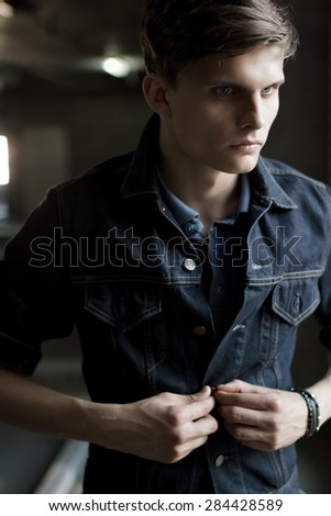 Stylish man in a denim jacket buttoning