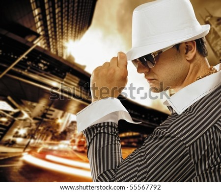 Stylish man in a hat in front of night city - stock photo