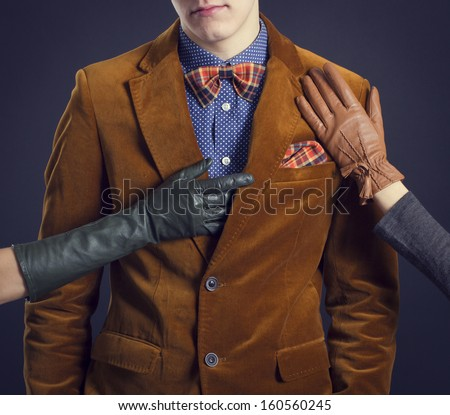 Stylish man in a red suit and women's hands in leather gloves. - stock photo