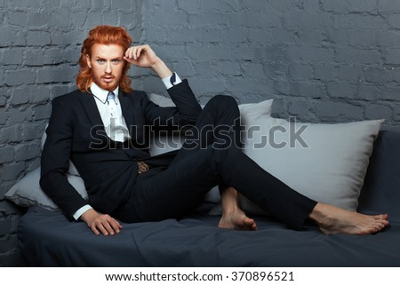 Stylish man in a suit with freckles on his face and beard. The business suit lying on the bed. - stock photo