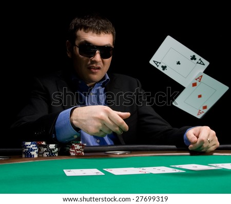 Stylish man in black suit folds two aces in casino poker at Las Vegas over black - stock photo