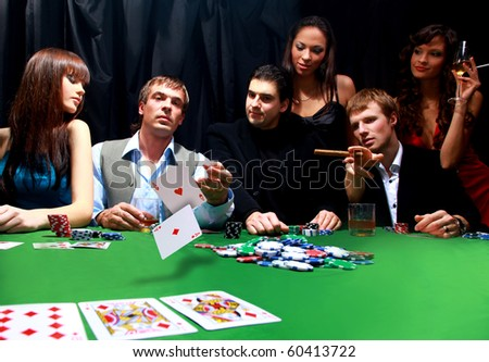 Stylish man in black suit folds two cards in casino poker at Las Vegas over black - stock photo