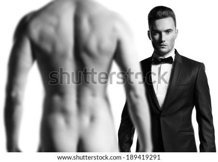 Stylish man in black suit in front of nude athletic male model - stock photo