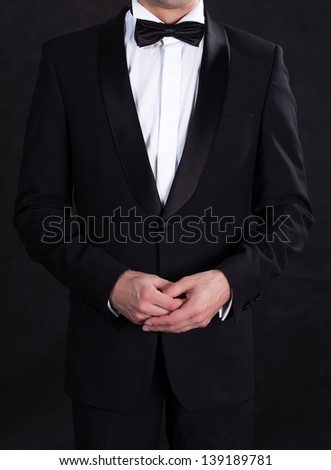 Stylish man in elegant black tuxedo, on black background
