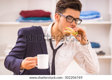 Stylish man in glasses eating his breakfast while hurring to work. - stock photo