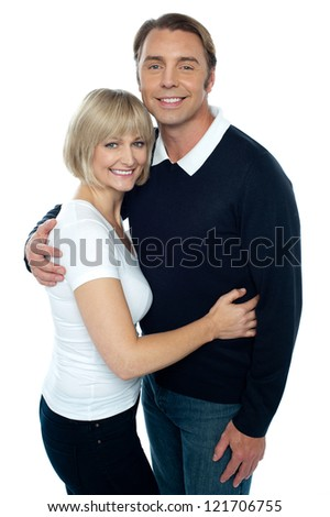 Stylish man in pullover embracing his blonde wife. Both smiling at the camera. - stock photo