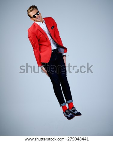 Stylish man in red jacket having fun jumping  - stock photo