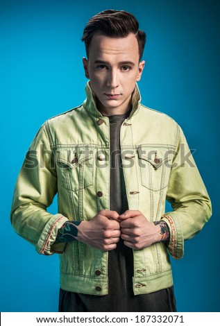 Stylish man in street style clothes on blue background - stock photo