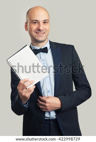 stylish man in suit and bow tie shows a blank sheet of notepad - stock photo
