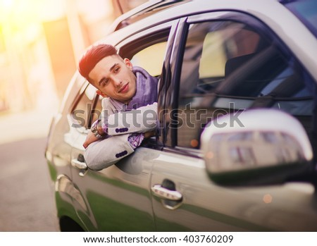 Stylish man in the car waiting for someone with a happy look