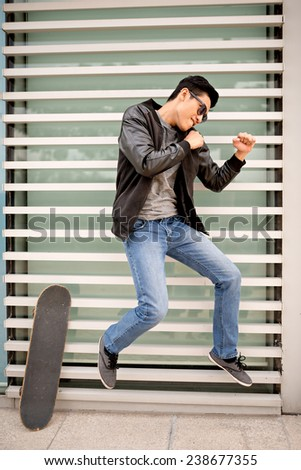 Stylish man jumping and pretending to be ready to fight - stock photo