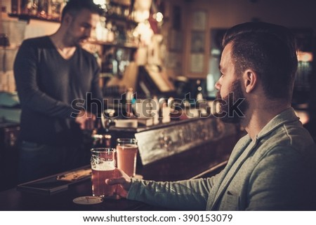 Stylish man sitting alone at bar counter with a pint of light beer.  - stock photo